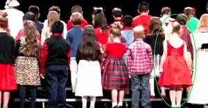 Copiii îşi ocupă locurile pe scenă. Când se întorc spre public, fetiţa în rochie roşie este cea care atrage toate privirile!
