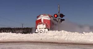 Un bărbat filmează trenul venind cu viteză, apoi surprinde momentul uimitor când spulberă zidul de zăpadă