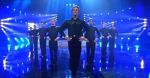 9 bărbaţi îşi ocupă locurile pe scenă. Dar priviţi-l pe dansatorul principal când apar femeile cu tobe!