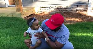 Tatăl se pregăteşte să-şi aşeze fetiţa pe iarbă. Reacţia micuţei stârneşte zâmbetele tuturor