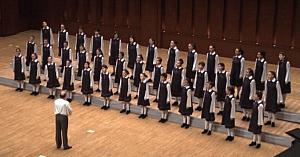 39 de fetiţe îşi ocupă locurile pe scenă. Câteva momente mai târziu publicul e fermecat de vocile lor angelice