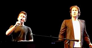 Josh Groban îi înmânează microfonul unui tânăr din public. Se schimbă la faţă când îl aude cântând primele note