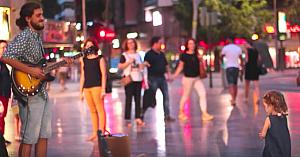 Fetiţa se apropie cu prudenţă de un artist stradal. În scurt timp mulţimea nu-şi poate lua ochii de la ea